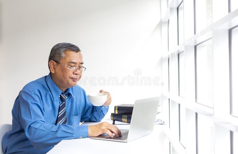 Un uomo che lavora in un bar Uomini al bar con laptop Uomo asiatico seduto in un bar impegnato a lavorare sul portatile immagini stock libere da diritti