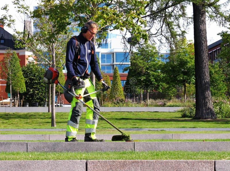 Un uomo che lavora a tagliare l'erba nella città di Umea fotografie stock