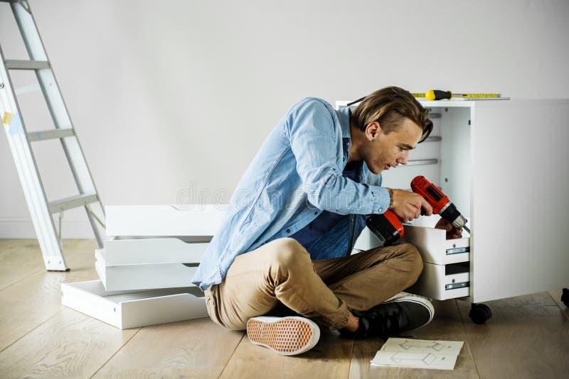 Un uomo che per mezzo del trapano elettronico installa la riparazione domestica del gabinetto immagine stock libera da diritti