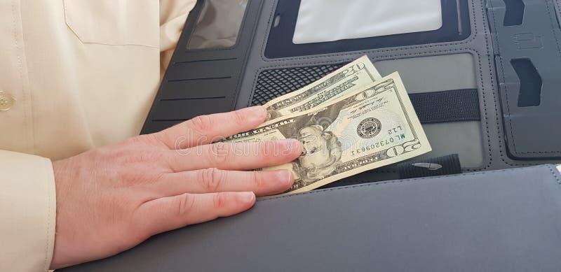 Un uomo che porta la camicia di colore chiaro ufficiale tiene il suo giusto NAND su venti dollari immagine stock libera da diritti