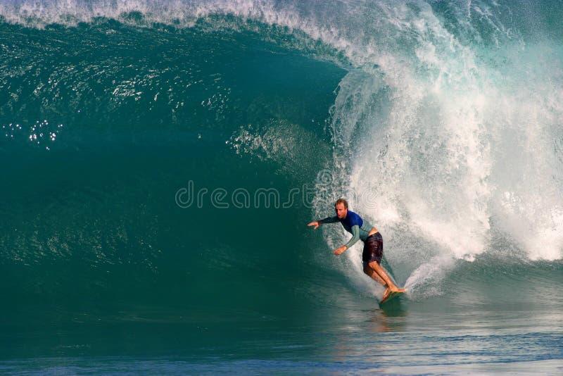 Un uomo che pratica il surfing un'onda blu in Hawai fotografia stock