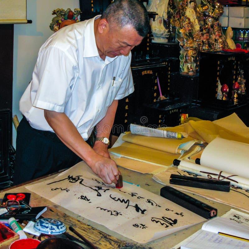 Un uomo che pratica l'arte antica della calligrafia cinese fotografia stock libera da diritti
