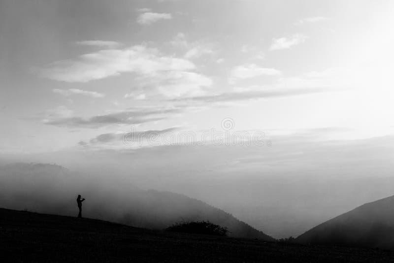 Un uomo che prende le foto su un picco di montagna, con nebbia e appanna tutta l'AR fotografie stock