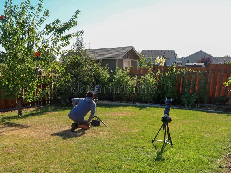 Un uomo che prende le immagini di un'eclissi solare totale su un cortile della casa fotografia stock libera da diritti