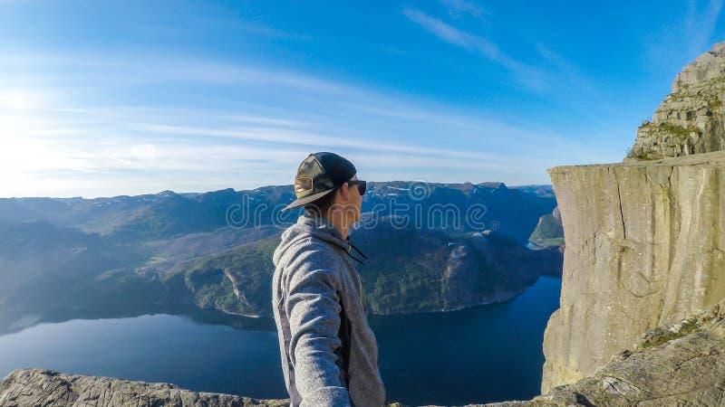 Un uomo che prende un selfie e che fa un'escursione lungo un fiordo in Norvegia Davanti lui è la montagna famosa di Preikestolen fotografie stock libere da diritti