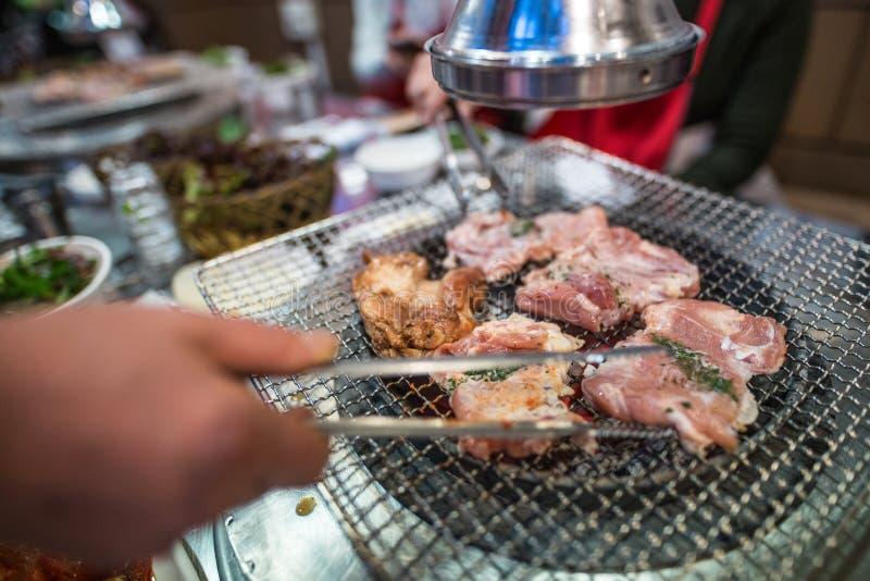 Un uomo che prepara cena grigliando carne immagini stock libere da diritti