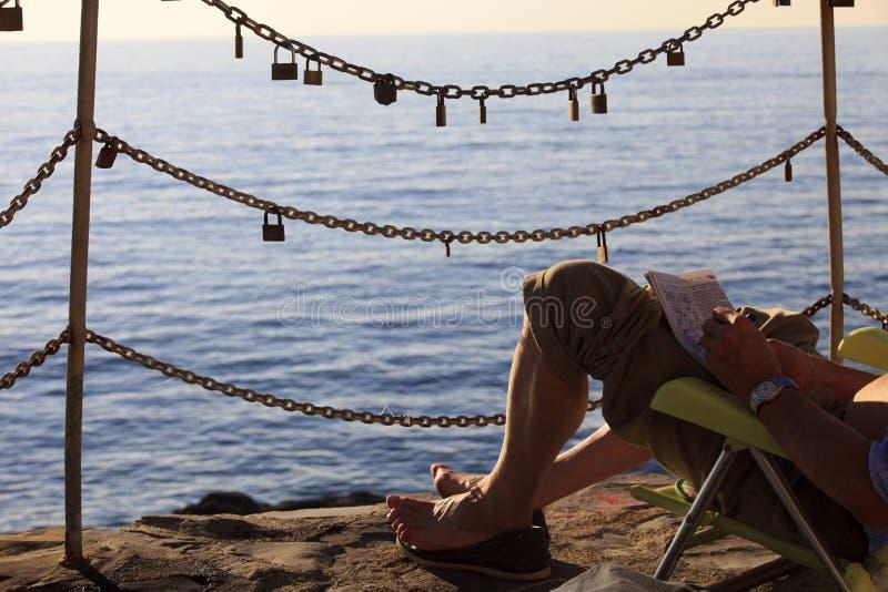 Un uomo che si rilassa nel paesino di pescatori di Camogli, golfo di Paradise, parco nazionale di Portofino, Genova, Liguria, Ita immagine stock
