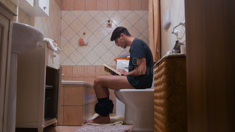 Un uomo che si siede sulla toilette e che legge un libro fotografia stock libera da diritti