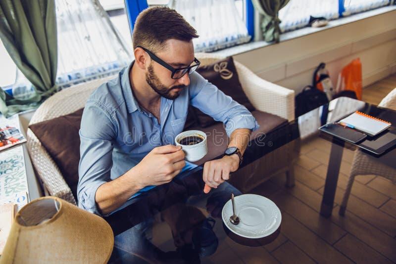 Un uomo che si siede in un caffè e che esamina il suoi orologio e caffè della bevanda immagini stock