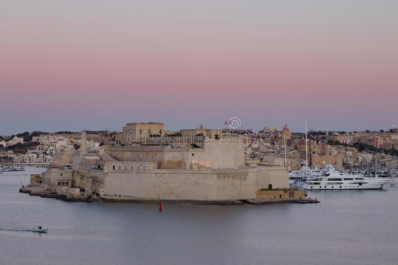 Un uomo che si siedono su un banco e che esaminano st forte Angelo ed il grande porto in Vittoriosa, Malta fotografie stock libere da diritti