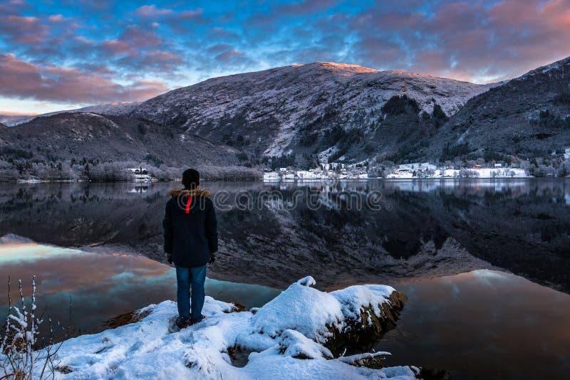 Un uomo che sta da solo dal lago nell'inverno al crepuscolo immagini stock libere da diritti