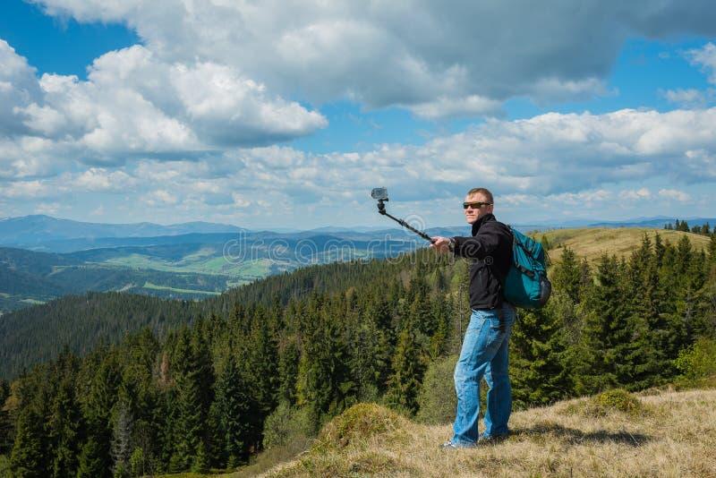 Un uomo che sta sulla cima di alta collina con la macchina fotografica di azione - fare selfie, su in montagne belle natura e nuv immagine stock libera da diritti