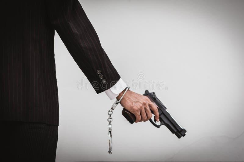 Un uomo che tiene una pistola a disposizione, la nave pronta a sparare all'uomo ha indicato una pistola fotografia stock