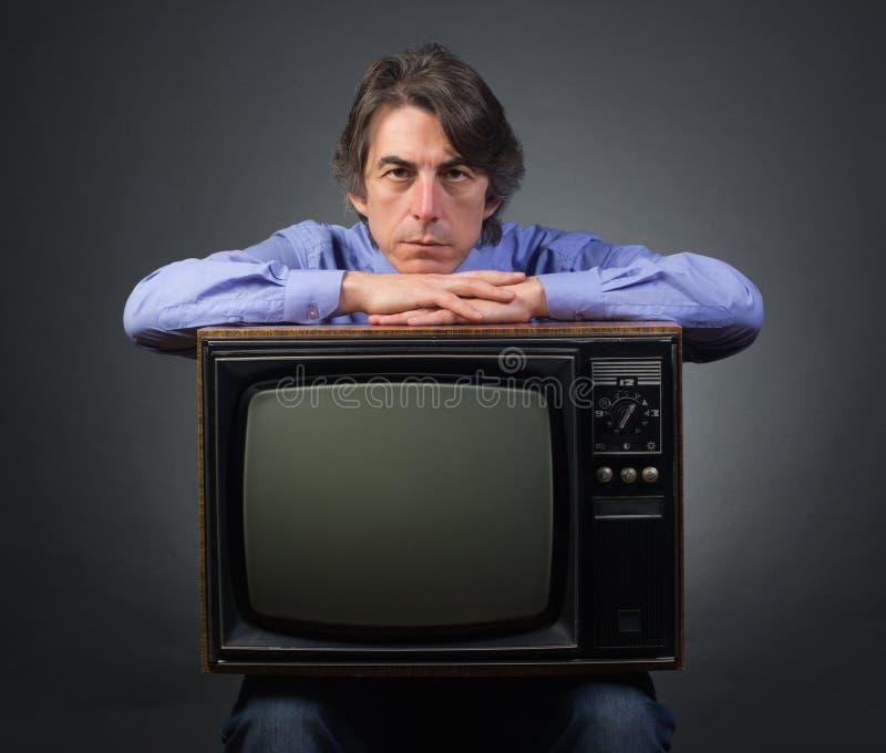 Un uomo che tiene una retro televisione immagini stock