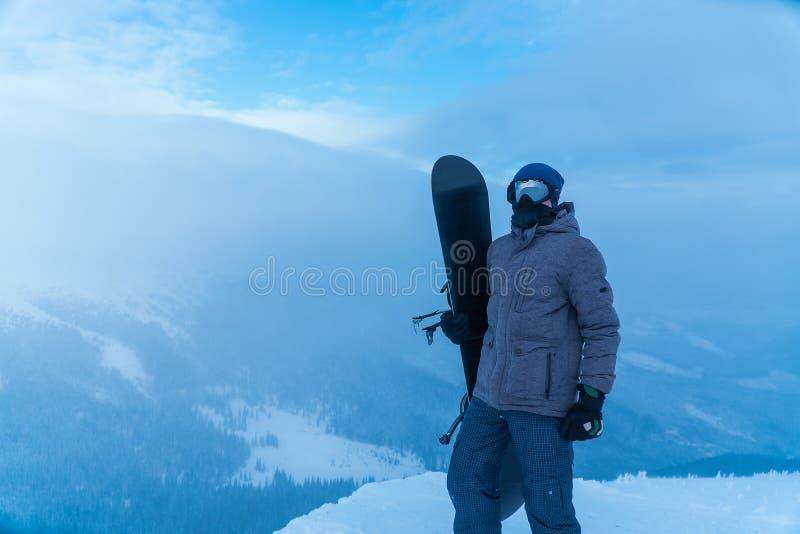 Un uomo che tiene uno snowboard a disposizione Snowboarder nelle montagne immagine stock