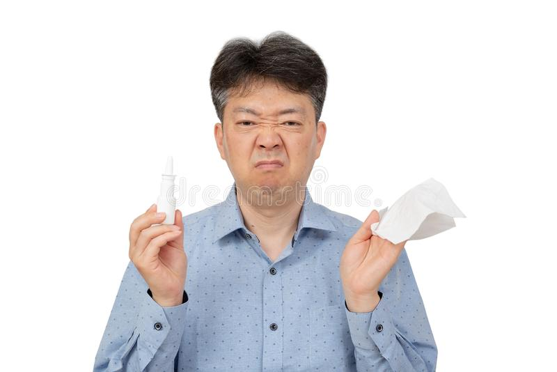 Un uomo che tiene uno spray nasale in sua mano su fondo bianco immagini stock libere da diritti