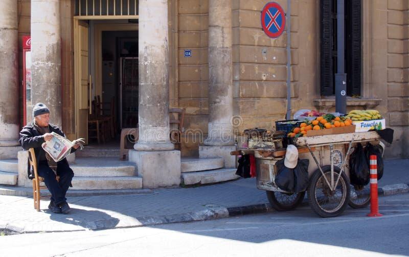 Un uomo che vende la frutta da una stalla su un carretto si siede sulla pavimentazione a Nicosia Cipro su un angolo di strada che immagini stock libere da diritti