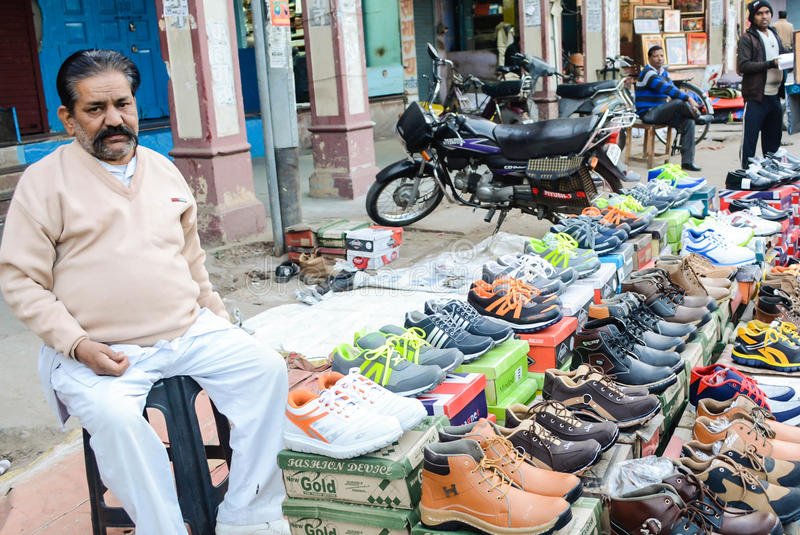 Un uomo che vende le scarpe immagine stock