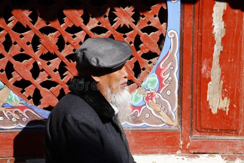 Un uomo cinese anziano con una barba caratteristica lungo la via nel villaggio di Shigu, il Yunnan, Cina fotografie stock