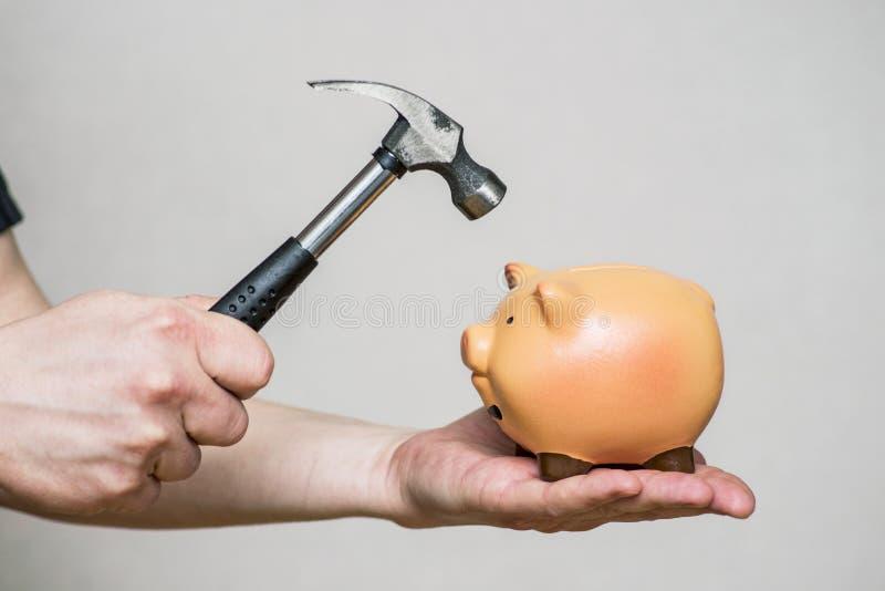 Un uomo circa per scassinare un porcellino salvadanaio ceramico con un grande martello Il porcellino salvadanaio si accinge a ? c fotografie stock libere da diritti