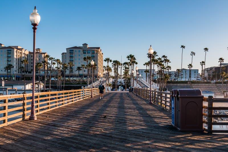 Un uomo comincia a camminare giù il pilastro di riva dell'oceano di mattina immagine stock