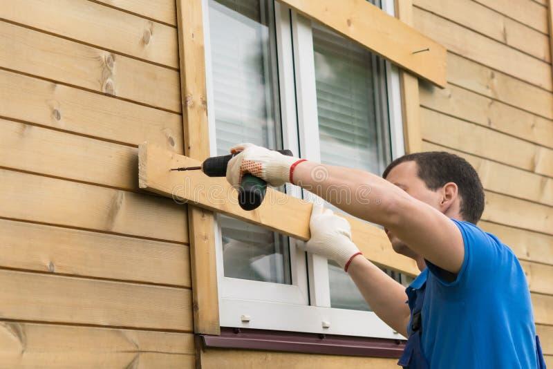 Un uomo con un cacciavite in sua mano sta bloccando le finestre della casa con i bordi, vista laterale fotografia stock libera da diritti