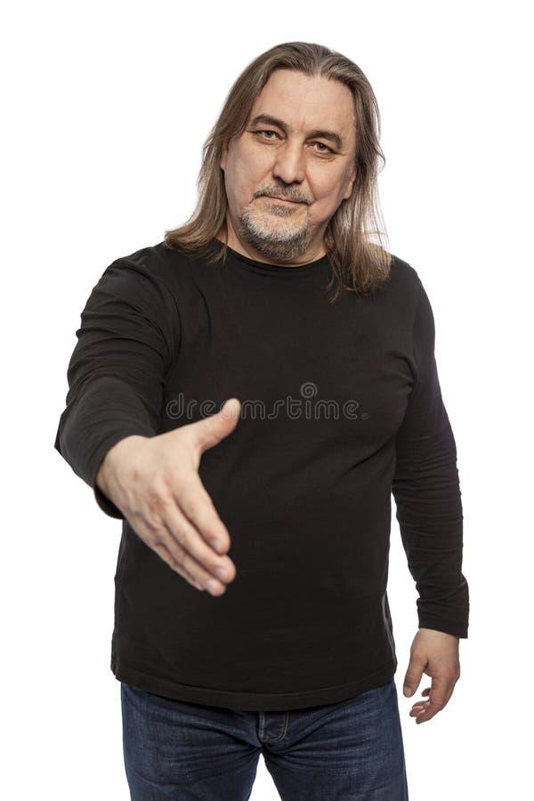 Un uomo con capelli lunghi di mezza età allunga fuori la sua mano per un saluto Isolato su una priorità bassa bianca fotografie stock
