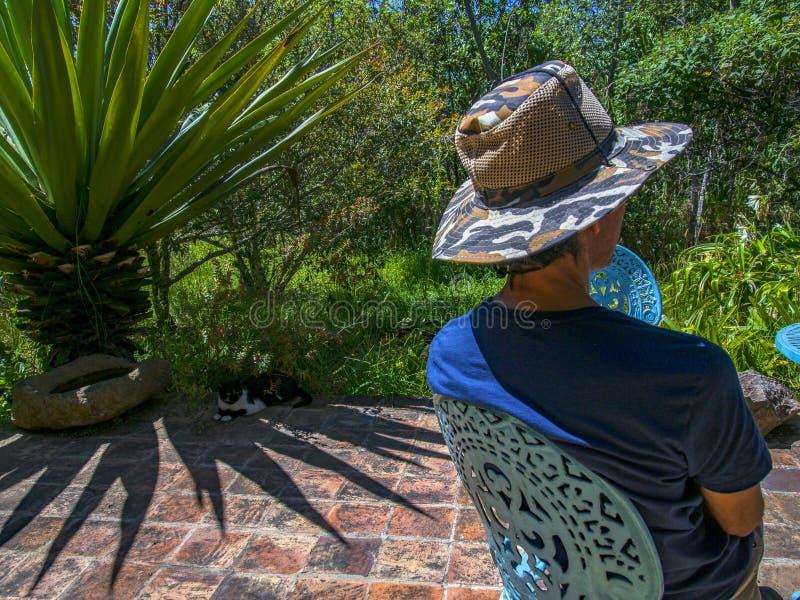 Un uomo con un cappello che si protegge dal sole di mezzogiorno fotografia stock