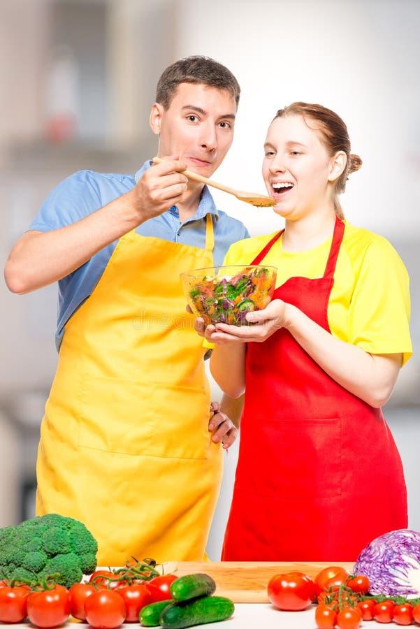 un uomo con un cucchiaio di legno alimenta una ragazza con un'insalata di verdure utile fotografia stock libera da diritti