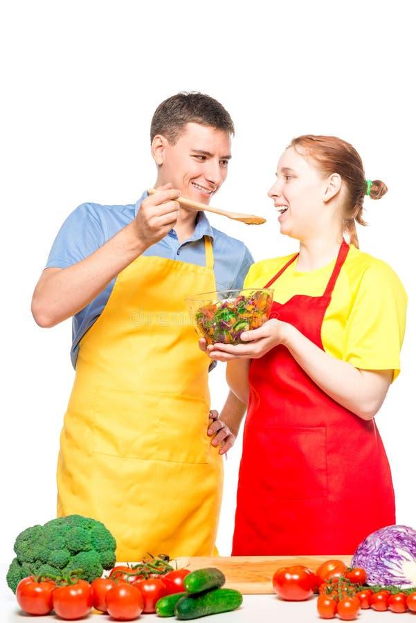 un uomo con un cucchiaio di legno e una ragazza con una ciotola di insalata provano l'alimento cucinato insieme su un bianco immagine stock libera da diritti