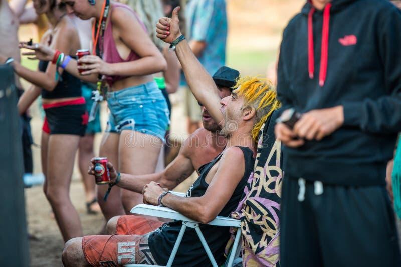 Un uomo con i ciuffi delle grida gialle dei capelli durante l'una delle sessioni del DJ al festival di musica perso dello psytran fotografie stock libere da diritti
