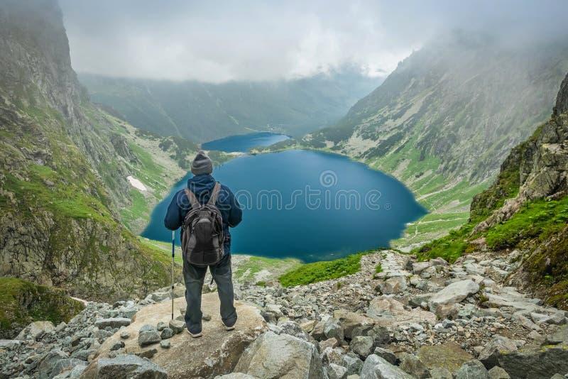 Un uomo con i pali di trekking che esaminano lago in montagne di Tatra fotografia stock libera da diritti