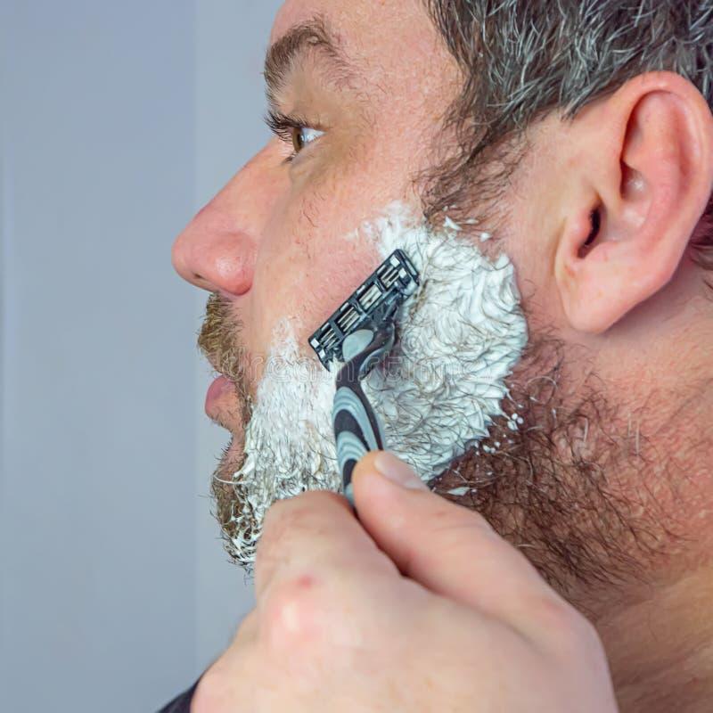 Un uomo con la barba grigia si rade fotografia stock