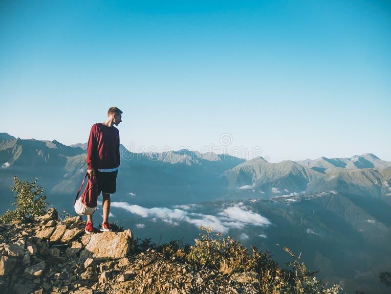 Un uomo con la maglietta rossa e i costumi neri sulla roccia bruna grande sulla cima di una montagna fotografia stock libera da diritti