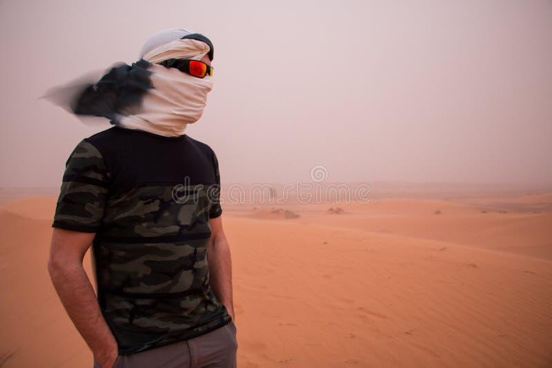 Un uomo con la sua testa coperta da un foulard e dagli occhiali da sole durante la tempesta di sabbia nel deserto immagini stock libere da diritti