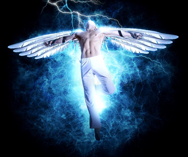 Un uomo con le ali sul fondo della luce di elettricità fotografie stock libere da diritti