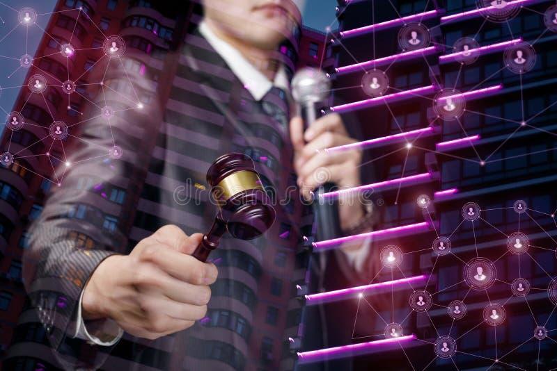 Un uomo con un martello e un microfono sta tenendo un'asta fotografia stock libera da diritti
