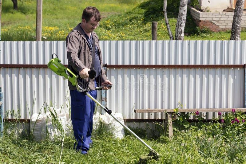 Un uomo con un regolatore falcia l'erba nell'iarda fotografia stock libera da diritti