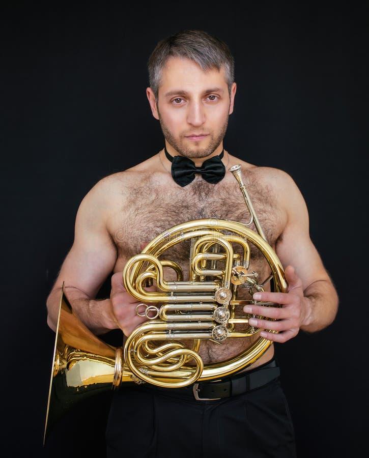Un uomo con un torso nudo in pantaloni ed in una farfalla tiene uno strumento musicale Waldhorn fotografia stock