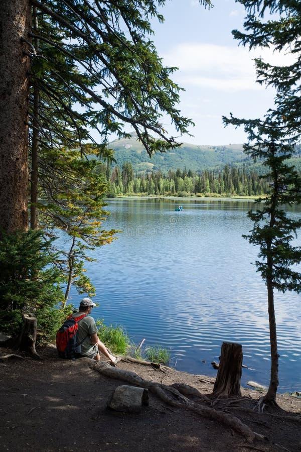 Un uomo con un lago alpino pieno d'ammirazione dello zaino Silver Lake, Uinta-W immagini stock