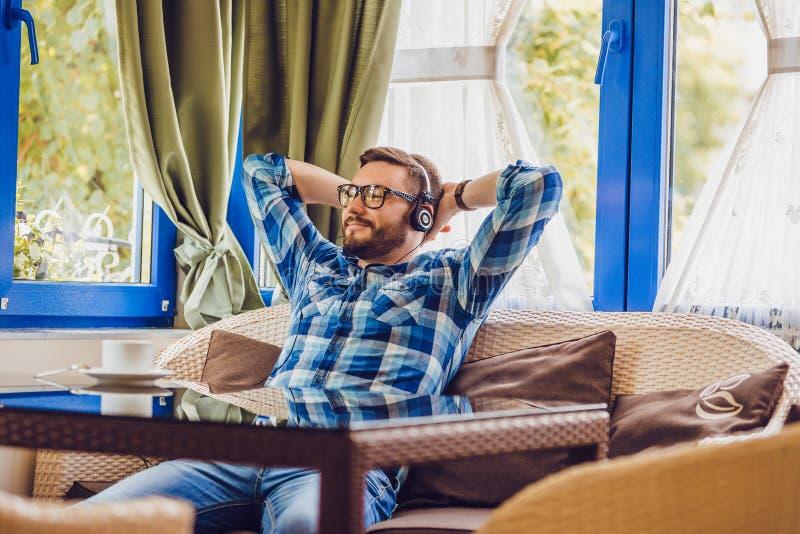 Un uomo con una barba che si siede nel caffè e che ascolta la musica, caffè bevente immagine stock