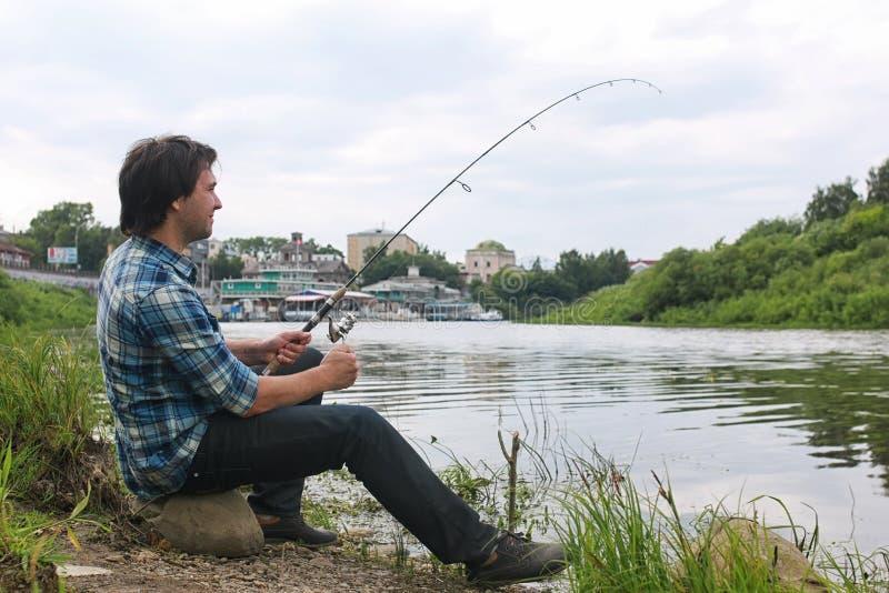 Un uomo con una barba sta pescando nel fiume fotografia stock