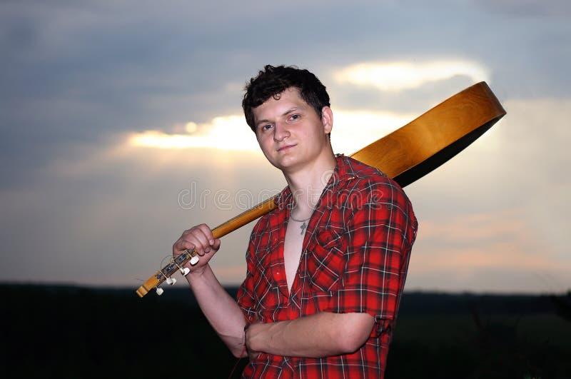 Un uomo con una chitarra al tramonto fotografie stock