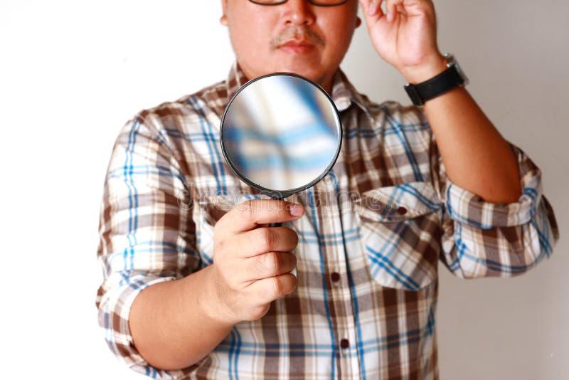 Un uomo con una lente di ingrandimento immagini stock