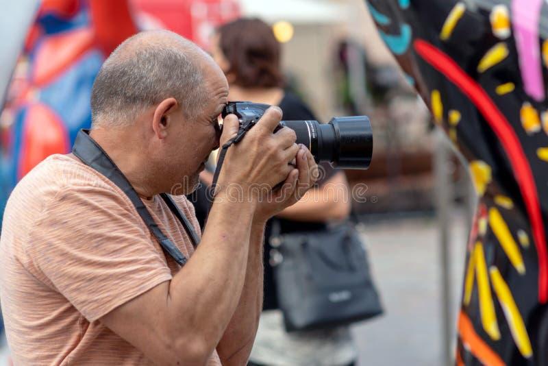 Un uomo con una macchina fotografica della foto fotografata sulla via fotografia stock