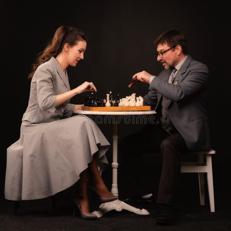 Un uomo con una ragazza gioca gli scacchi e fuma un tubo su un backgr scuro fotografie stock libere da diritti