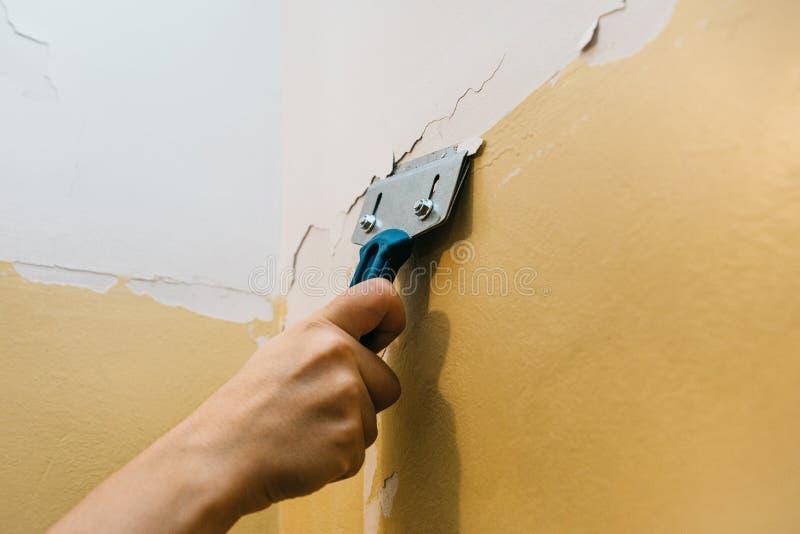 Un uomo con una ruspa spianatrice rimuove la vecchia copertura dalla parete immagine stock libera da diritti