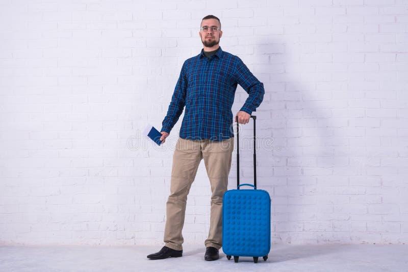 Un uomo con una valigia blu e un passaporto vicino ad un muro di mattoni bianco immagini stock