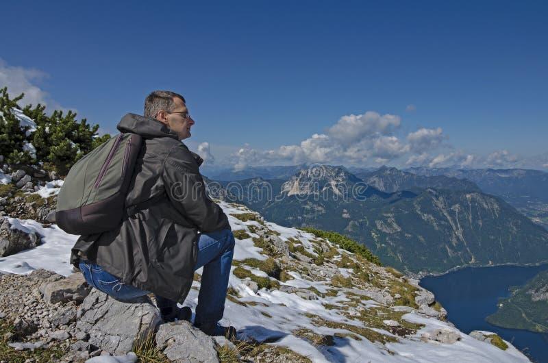 Un uomo con uno zaino che ammira un Mountain View immagine stock libera da diritti