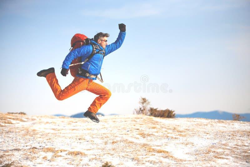 Un uomo con uno zaino salta sulla montagna del fondo immagini stock